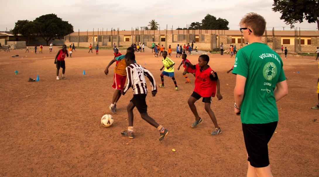 Projects Abroad High School Special volunteer referees a football match in Ghana during his Football Coaching project.